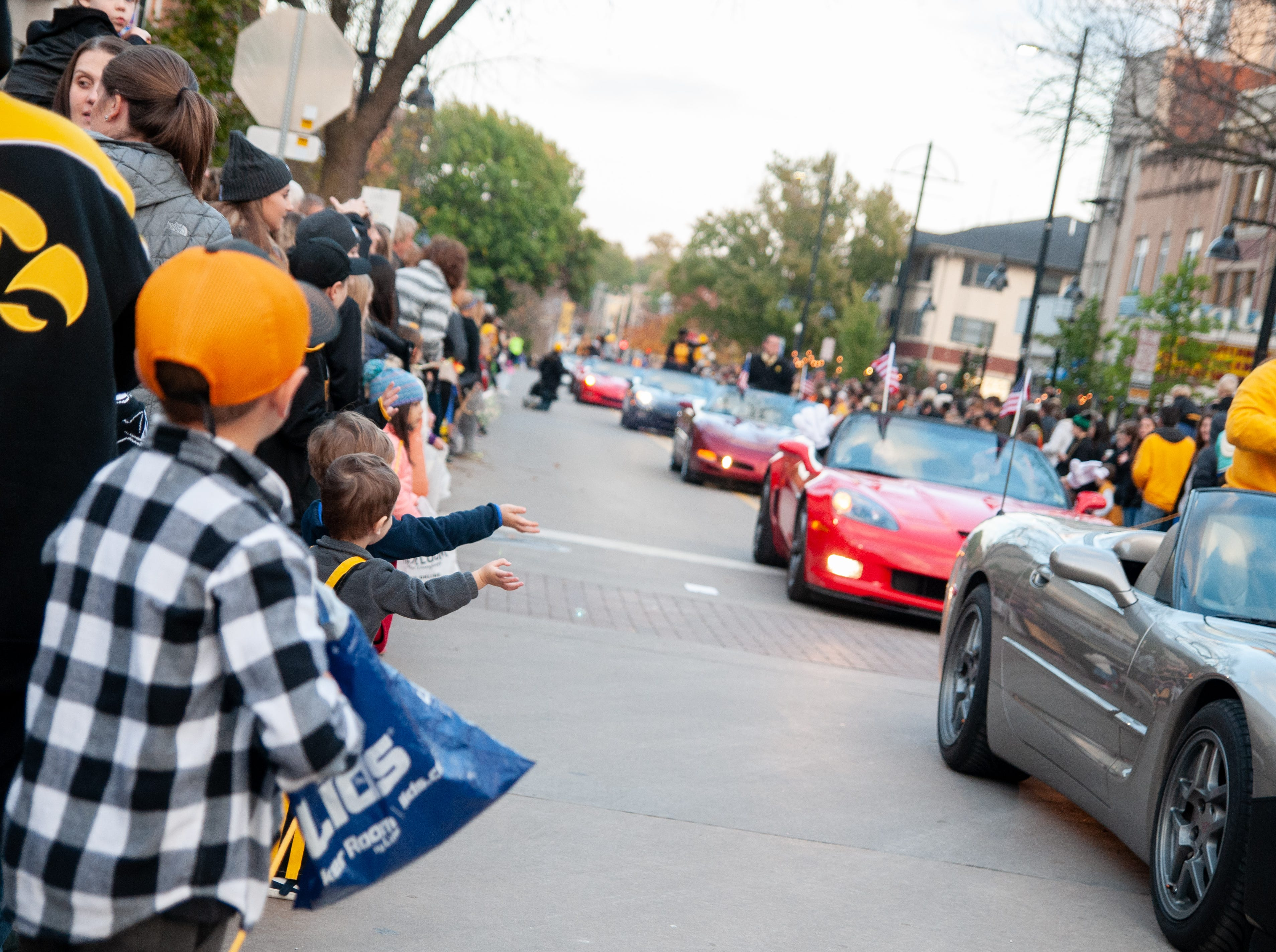 Distinguished Alumni Award recipients wave to crowd members during the 2018 Homecoming parade, Friday, Oct. 19, 2018, in Iowa City.