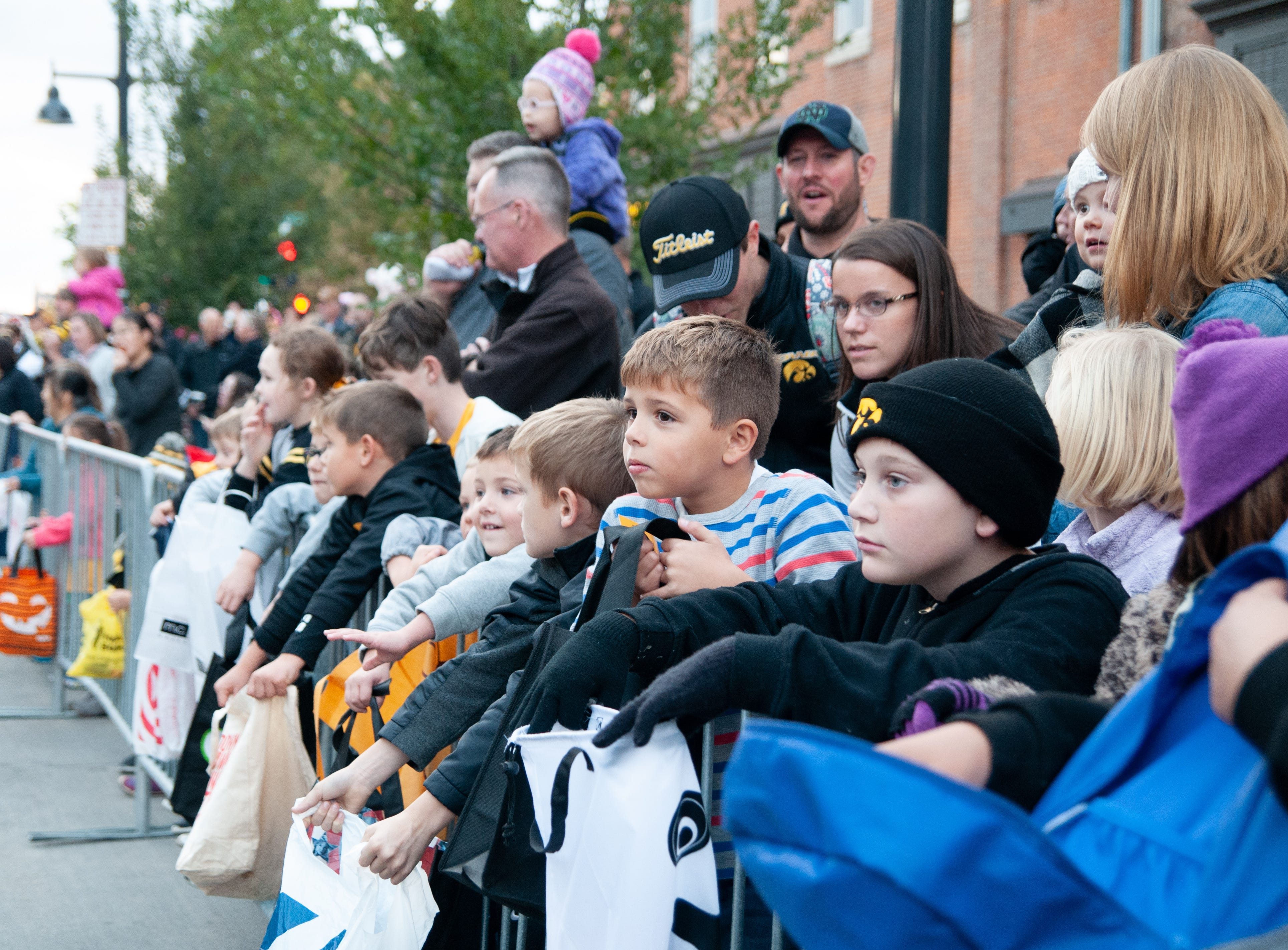 Kids line Washington Street for the 2018 Homecoming parade, Friday, Oct. 19, 2018, in Iowa City.
