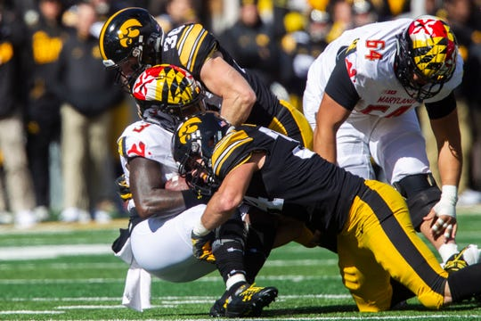 Iowa linebacker Kristian Welch (34) and Iowa defensive back Jake Gervase (30) tackle Maryland quarterback Tyrell Pigrome (3) during an NCAA Big Ten conference football game on Saturday, Oct. 20, 2018, at Kinnick Stadium in Iowa City.
