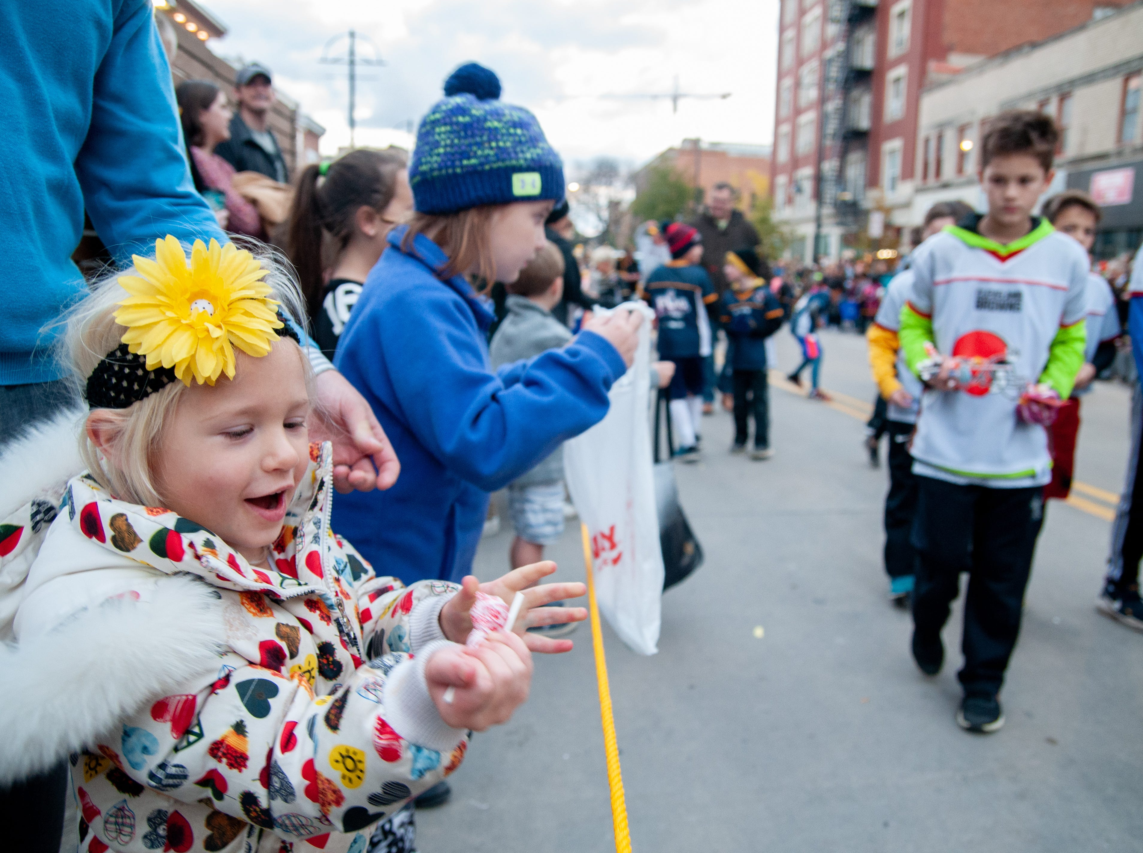 Audrea Beelner, 3, receives candy during the 2018 Homecoming parade, Friday, Oct. 19, 2018, in Iowa City.