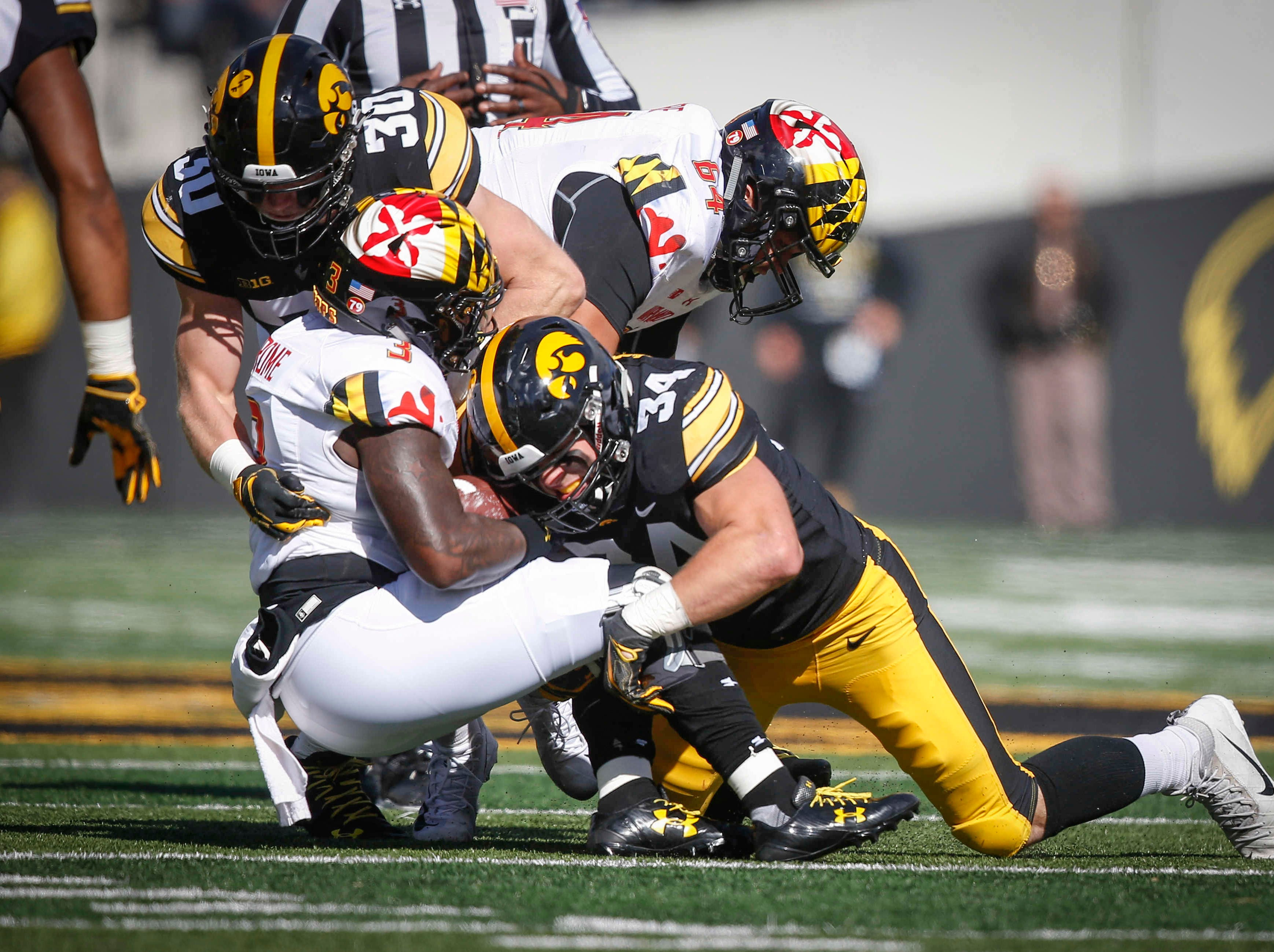 Iowa safety Jake Gervase (No. 30) and linebacker Kristian Welch team up to tackle Maryland quarterback Tyrrell Pigrome on Saturday, Oct. 20, 2018, at Kinnick Stadium in Iowa City.