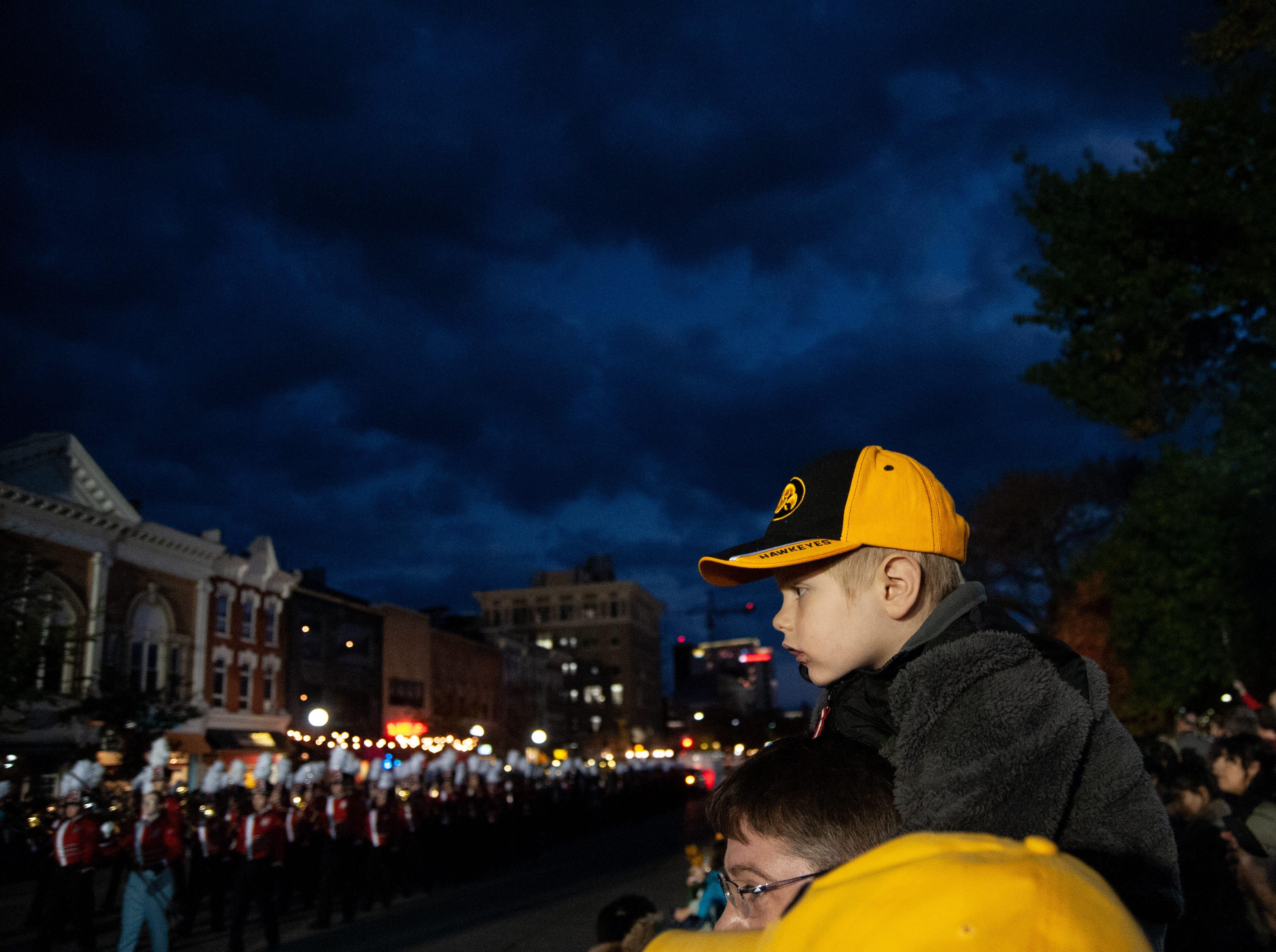 Luke Winborn, 4, rests on Brett Windorn, during the 2018 Homecoming parade, Friday, Oct. 19, 2018, in Iowa City.