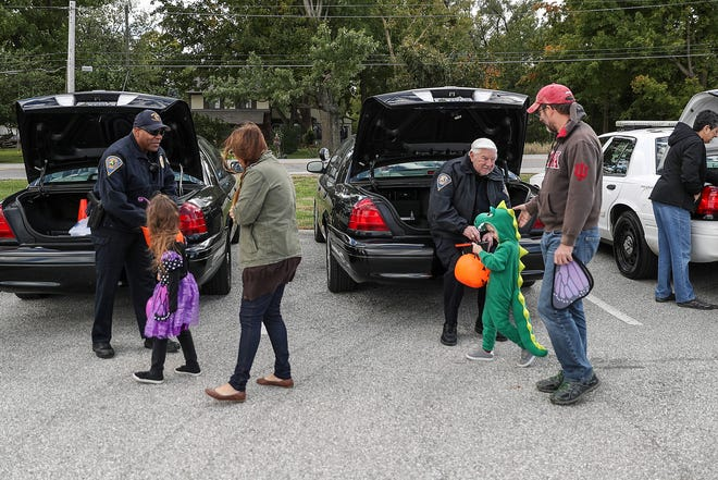 Children and families collect candy from Indiana law enforcement officers and firefighters during Trunk or Treat at the Indiana State Police Museum in Indianapolis, Saturday, Oct. 20, 2018.