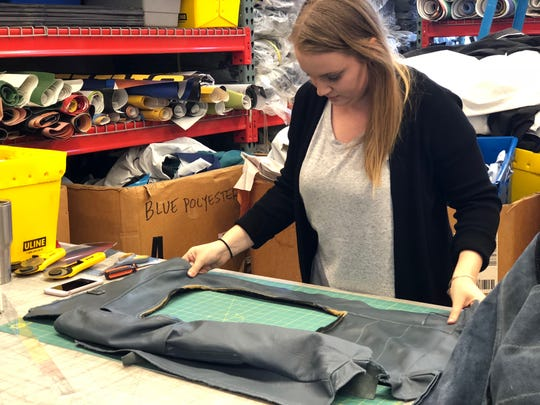 PUP materials assistant Sara Blythe measures leather from Amtrak train car seats for a bag.