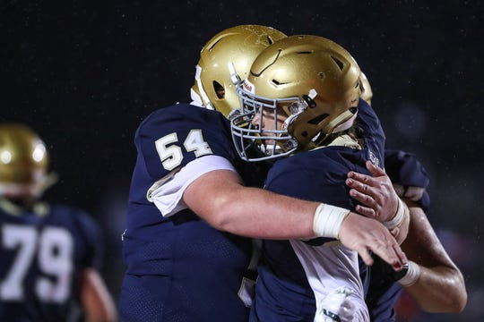 Cathedral Fighting Irish offensive lineman Jacob Schommer (54) and wide receiver Bo Sanders (5) celebrate Sanders' touchdown during the first half of sectionals at Southport High School in Indianapolis, Friday, Oct. 19, 2018. Cathedral won, 51-14.