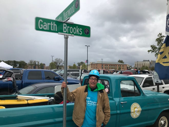 Mishawaka Mayor Dave Wood poses with Garth Brooks and Trisha Yearwood street signs during a Saturday afternoon tailgate party at Notre Dame Stadium.