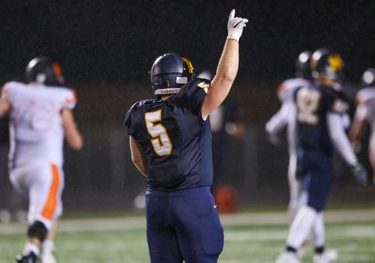 Mooresville Pioneers' Blake Garrett (5) raises his hand as teammate Jon Eineman (11) scores a touchdown against the Beech Grove Hornets at Mooresville High School on Friday, Oct. 19, 2018.