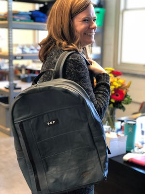 PUP Director of Design and Fabrication Jessica Bricker models one of the backpacks made from resused Amtrak seat leather.
