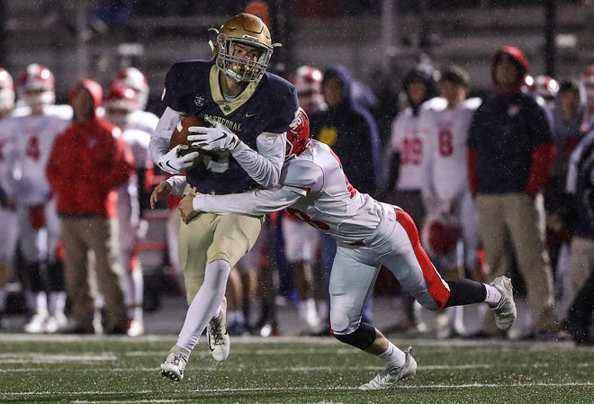 Cathedral Fighting Irish wide receiver Bo Sanders (5) is pulled down by Plainfield Quakers Dylan Swanson (28) during the first half of sectionals at Southport High School in Indianapolis, Friday, Oct. 19, 2018. Cathedral won, 51-14.