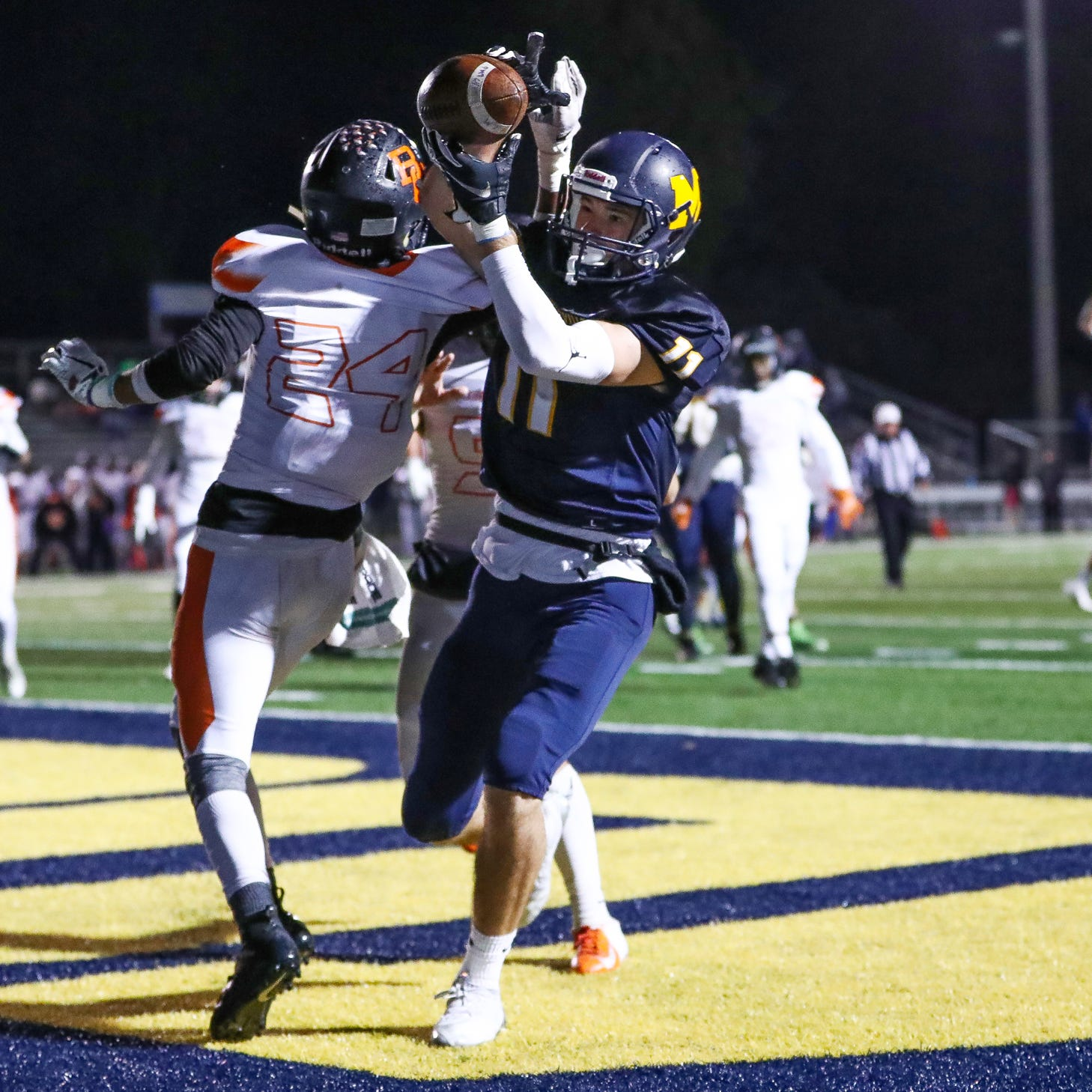 Mooresville Pioneers' Jon Eineman (11) goes up and over Beech Grove Hornets' Donovan Bailey (24) for the touchdown at Mooresville High School on Friday, Oct. 19, 2018.