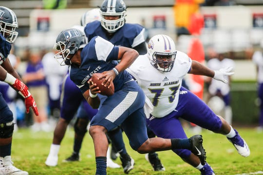 JSU quarterback Jarrad Hayes looks to elude the grasp of UNA defender Eddquerion Harris.