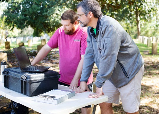 In this Oct. 12, 2018 photograph, Stephen Harris, a research associate at the University of Mississippi, and professor Tony Boudreaux, Director of the Center for Archaeological Research at the University of Mississippi, discuss results from the archaeological study being conducted at Friendship Cemetery in Columbus, Miss. (Laura Daniels/The Commercial Dispatch via AP)