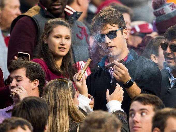 Alabama fans light cigars during the Tennessee Volunteers' game against Alabama in Neyland Stadium on Saturday, October 20, 2018.