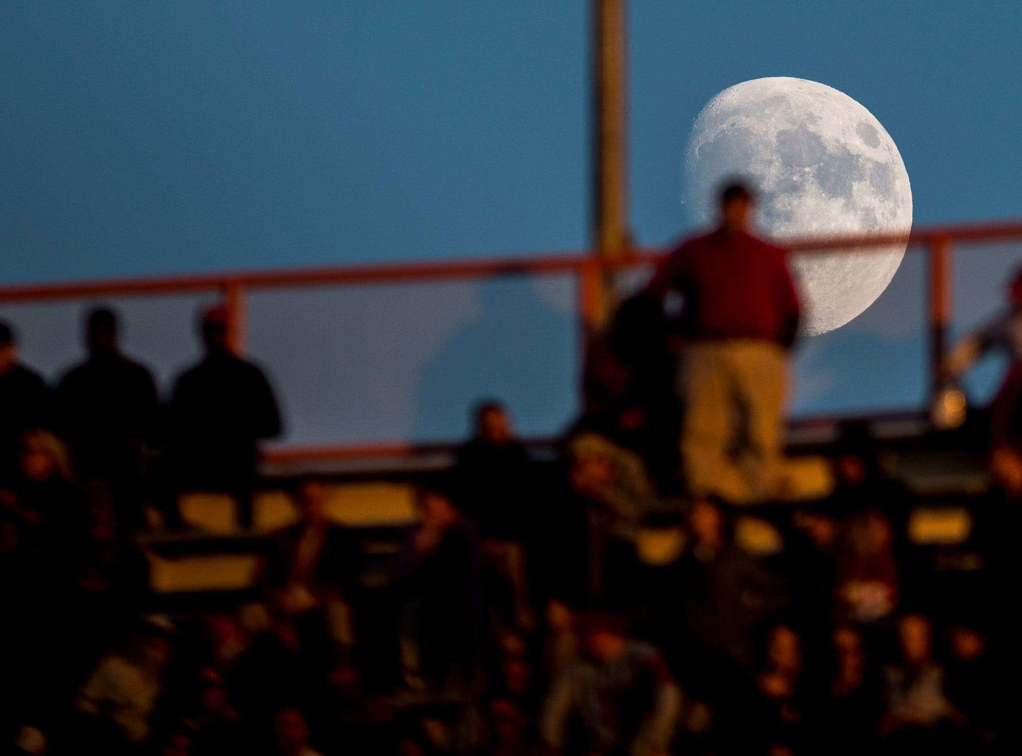 The moon rises behind a fan during a game between Tennessee and Alabama at Neyland Stadium in Knoxville, Tennessee on Saturday, October 20, 2018.