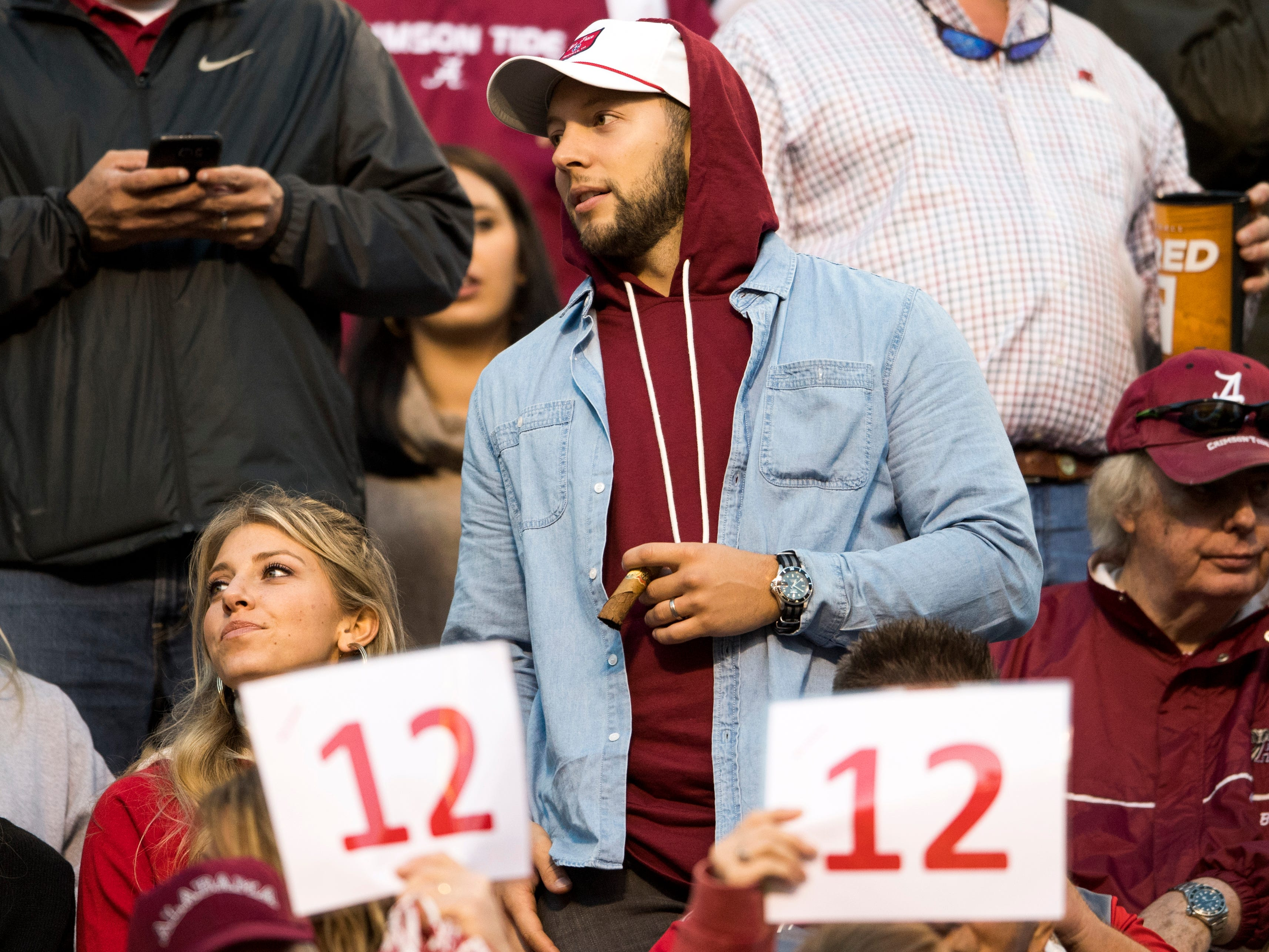 """Alabama fans light cigars and hold up signs with """"12"""" on them, signifying the 12-game win streak against Tennessee, during the Tennessee Volunteers' game against Alabama in Neyland Stadium on Saturday, October 20, 2018."""