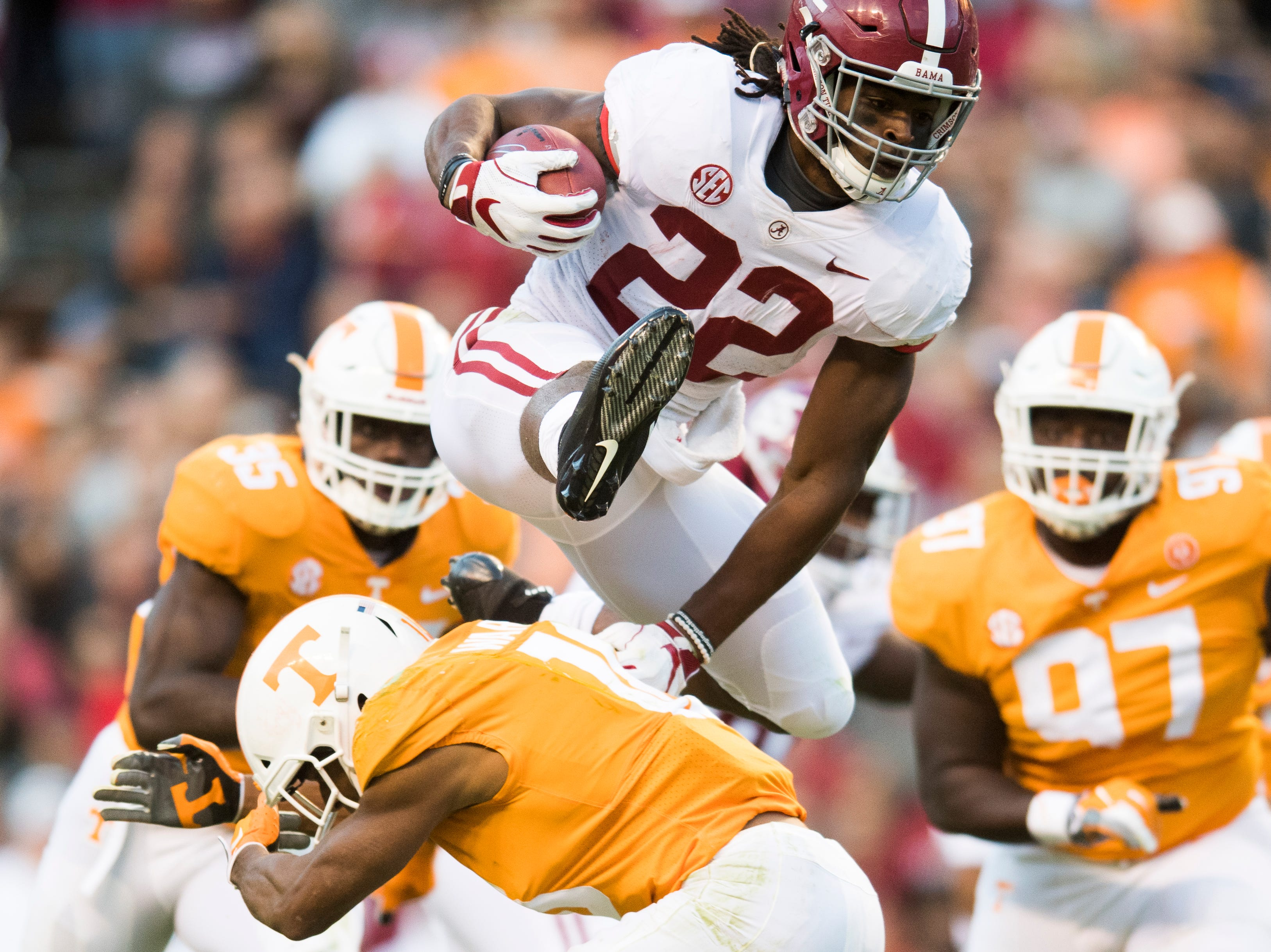 Alabama running back Najee Harris (22) leaps over Tennessee defensive back Nigel Warrior (18) during a game between Tennessee and Alabama at Neyland Stadium in Knoxville, Tennessee on Saturday, October 20, 2018.