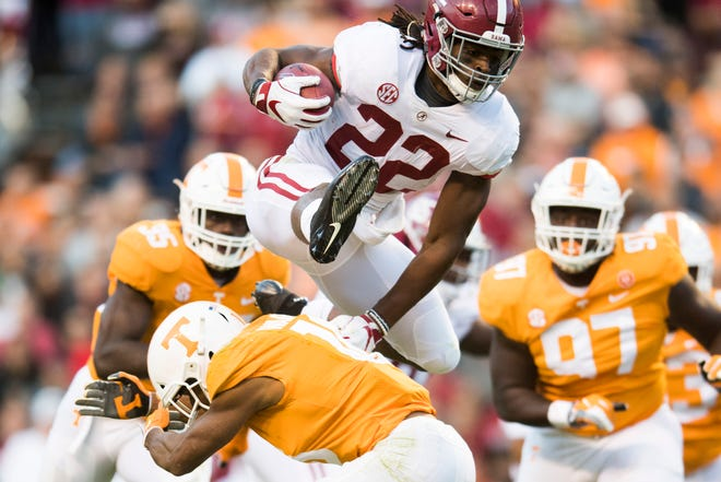 Alabama running back Najee Harris (22) leaps over Tennessee defensive back Nigel Warrior (18) during the Crimson Tide's 58-21 win over the Volunteers on Saturday at Neyland Stadium.