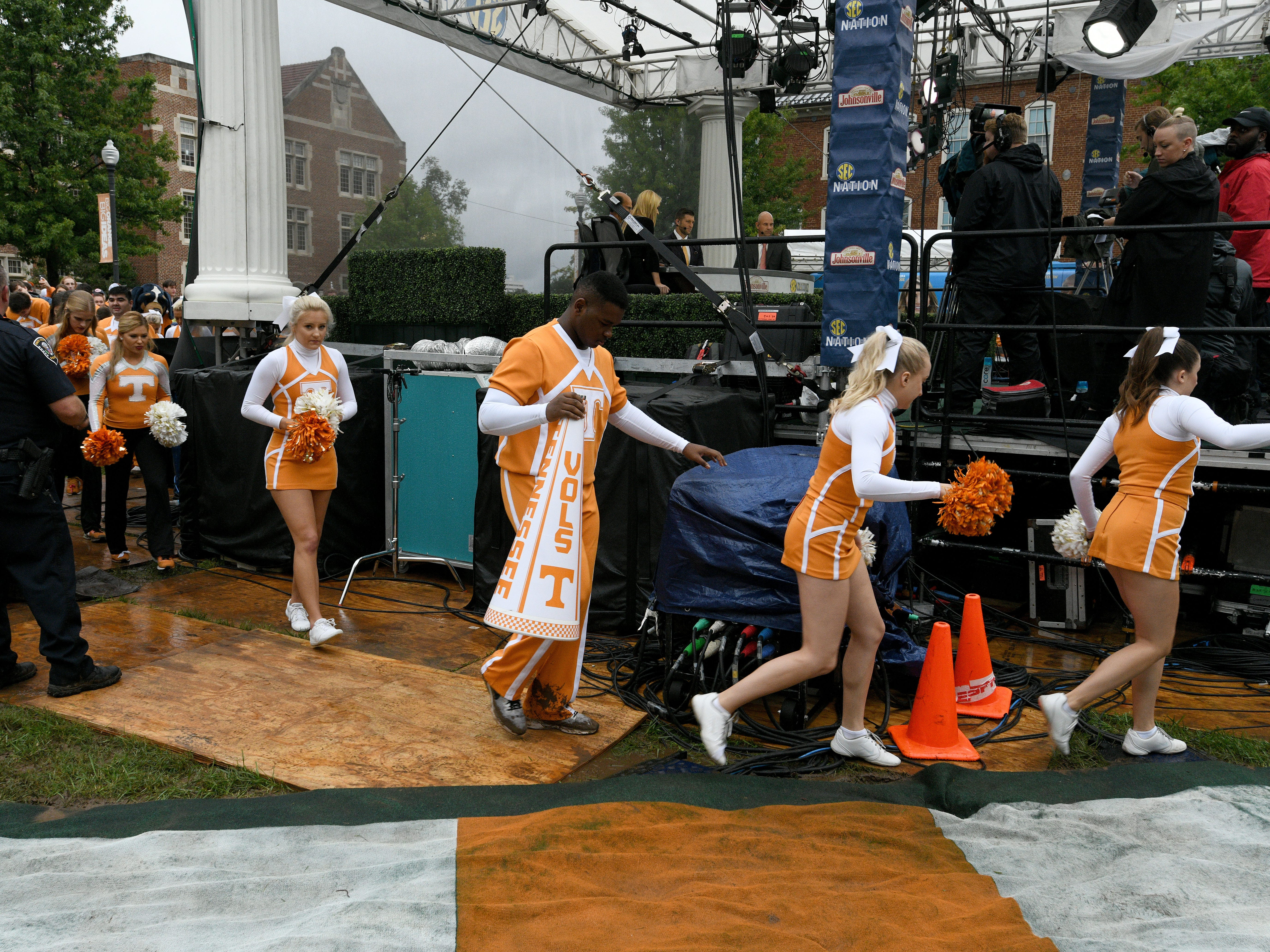 Tennessee cheerleaders navigate the mud during their appearance on the SEC Nation show at Ayers Hall before the Alabama game Saturday, October 20, 2018 at Neyland Stadium in Knoxville, Tenn.