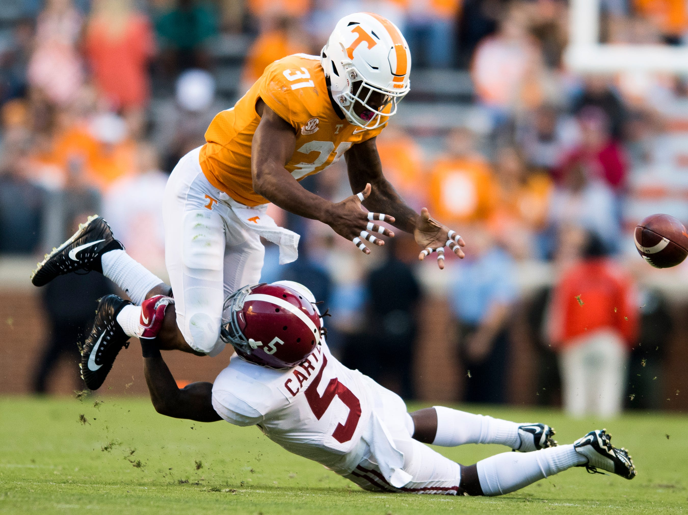 Tennessee running back Madre London (31) loses the ball as Alabama defensive back Shyheim Carter (5) tackles him during a game between Tennessee and Alabama at Neyland Stadium in Knoxville, Tennessee on Saturday, October 20, 2018.