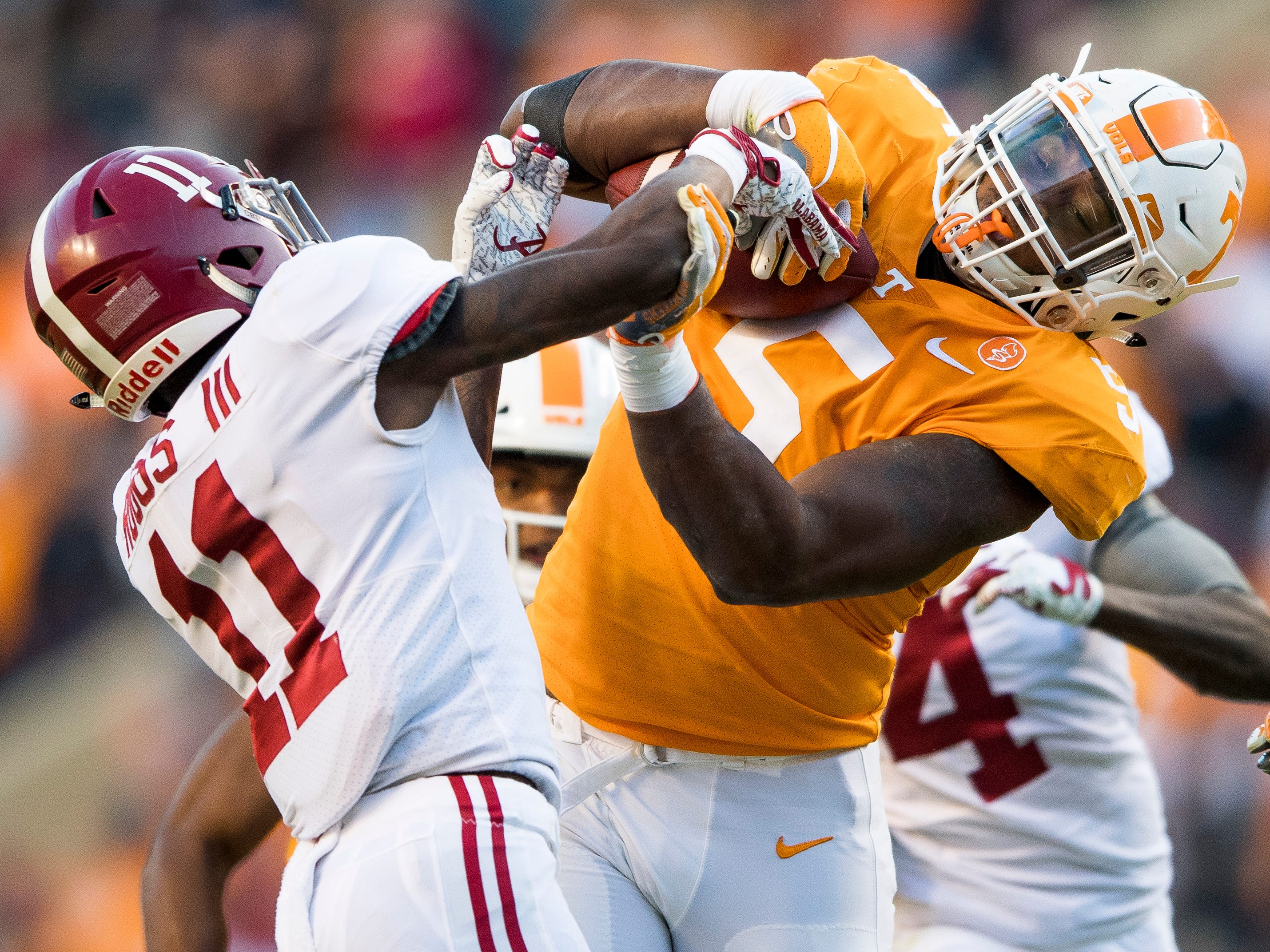 Alabama wide receiver Henry Ruggs III (11) tries to pry the ball out of the hand of Tennessee defensive lineman Kyle Phillips (5) as Phillips returns an interception in for a touchdown during the Tennessee Volunteers' game against Alabama in Neyland Stadium on Saturday, October 20, 2018.