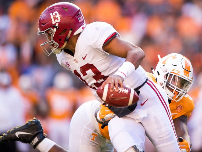 Alabama quarterback Tua Tagovailoa (13) escapes a tackle by Tennessee defensive lineman Kyle Phillips (5) during the Tennessee Volunteers' game against Alabama in Neyland Stadium on Saturday, October 20, 2018.