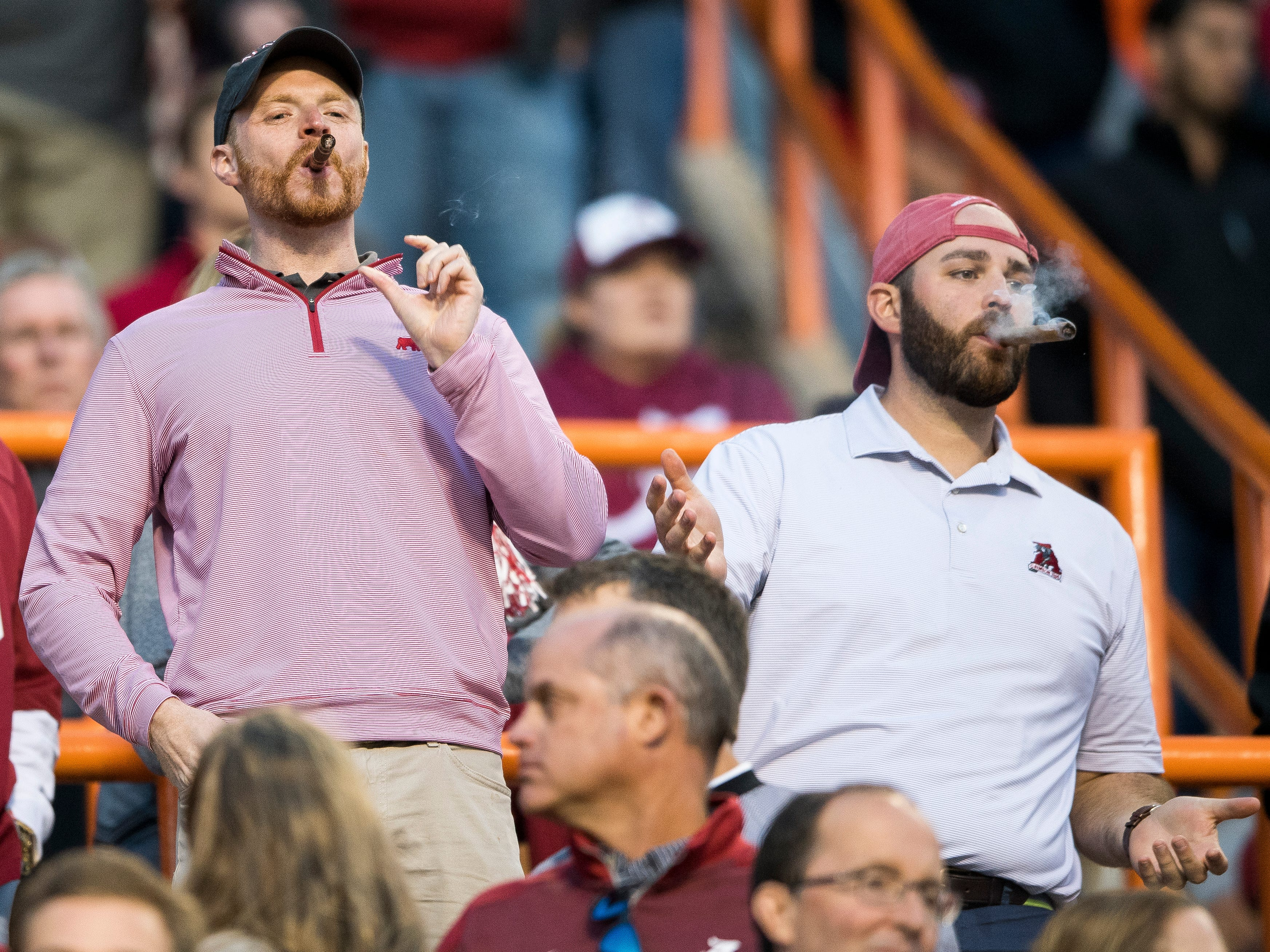 Alabama fans smoke cigars during the Tennessee Volunteers' game against Alabama in Neyland Stadium on Saturday, October 20, 2018.
