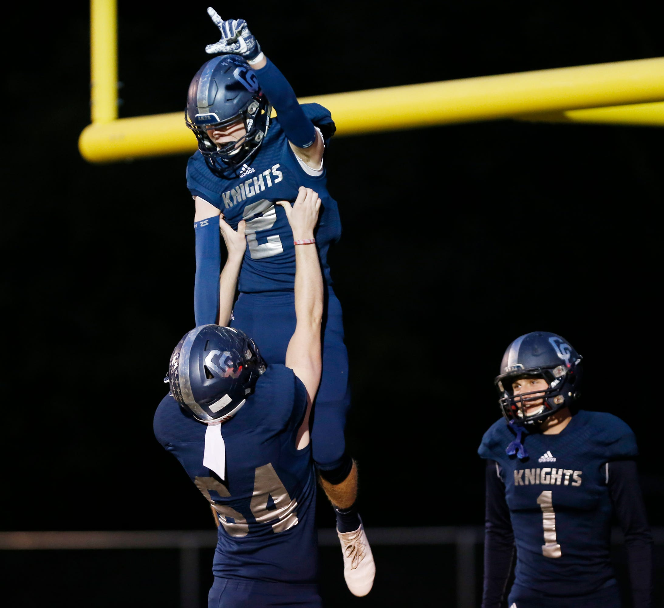 Scott Lovell of Central Catholic is lifted into the air by teammate Michael Beardmore after his touchdown reception at 8:03 in the first quarter against North White in the football sectional Friday, October 19, 2018, in Lafayette.
