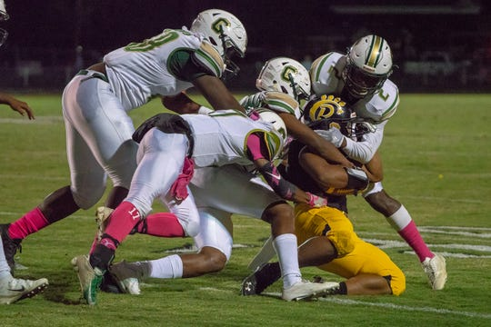 Church Point's Rodney Dupuis is tackled by a group of defenders as the Church Point Bears play at home against the Crowley Gents on October 18, 2018.