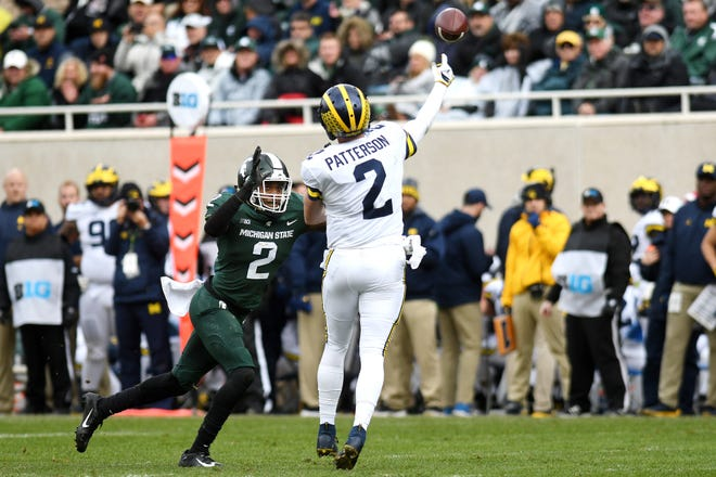 Michigan State's Justin Layne, left, pressures Michigan's Shea Patterson during the second quarter on Saturday, Oct. 20, 2018, in East Lansing.