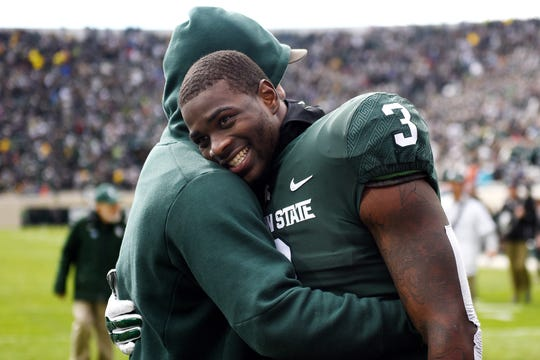MSU running back LJ Scott, right, hugs former MSU linebacker Chris Frey at the beginning of the weather delay during last week's game against Michigan.