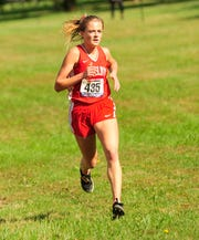 Shelby's Makenna Heimlich crosses the finish line during the Cross Country District Tournament at Galion on Saturday.