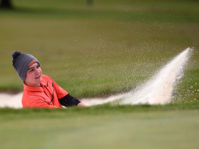 Ashland's Max Watson blasts out of a greenside bunker on the 14th hole during the Division I state golf tournament at Ohio State's Scarlet Course. Watson, an Eastern Michigan recruit, shot a 77 and is tied for fifth place.
