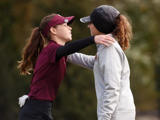 New Albany's Madison Spiess, left, and Ashland's Anna Watson share a hug on the 18th green following their rounds at the Division I state golf tournament on Saturday at Ohio State's Gray Course. Watson shot 76 to finish tied for eighth and earn second-team All-Ohio.