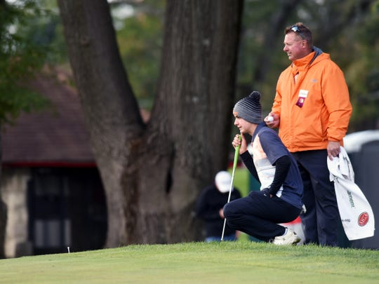 Ashland's Max Watson and his coach, David Chapman, read a putt on the 14th hole on Saturday during the Division I state golf tournament at Ohio State's Scarlet Course. Watson shot 80 to place ninth and earn second-team All-Ohio.
