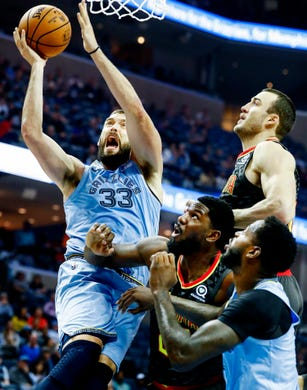 Memphis Grizzlies center Marc Gasol (left) drives for a lay-up against the Atlanta Hawks defense in their home-opener at the FedExForum in Memphis, Tenn., Friday, October 19, 2018.