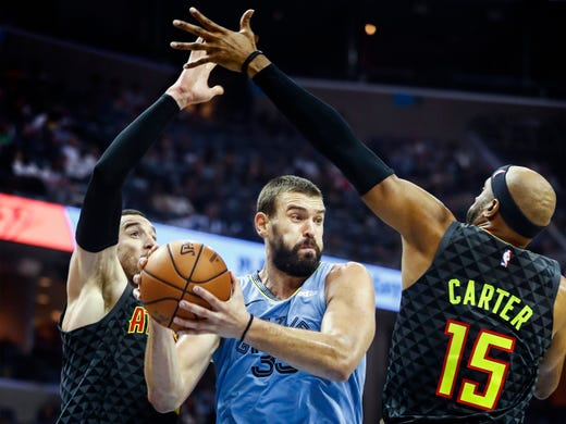 Memphis Grizzlies center Marc Gasol (middle) splits Atlanta Hawks defends Alex Len (left) and Vince Carter (right) in their home-opener at the FedExForum in Memphis, Tenn., Friday, October 19, 2018.
