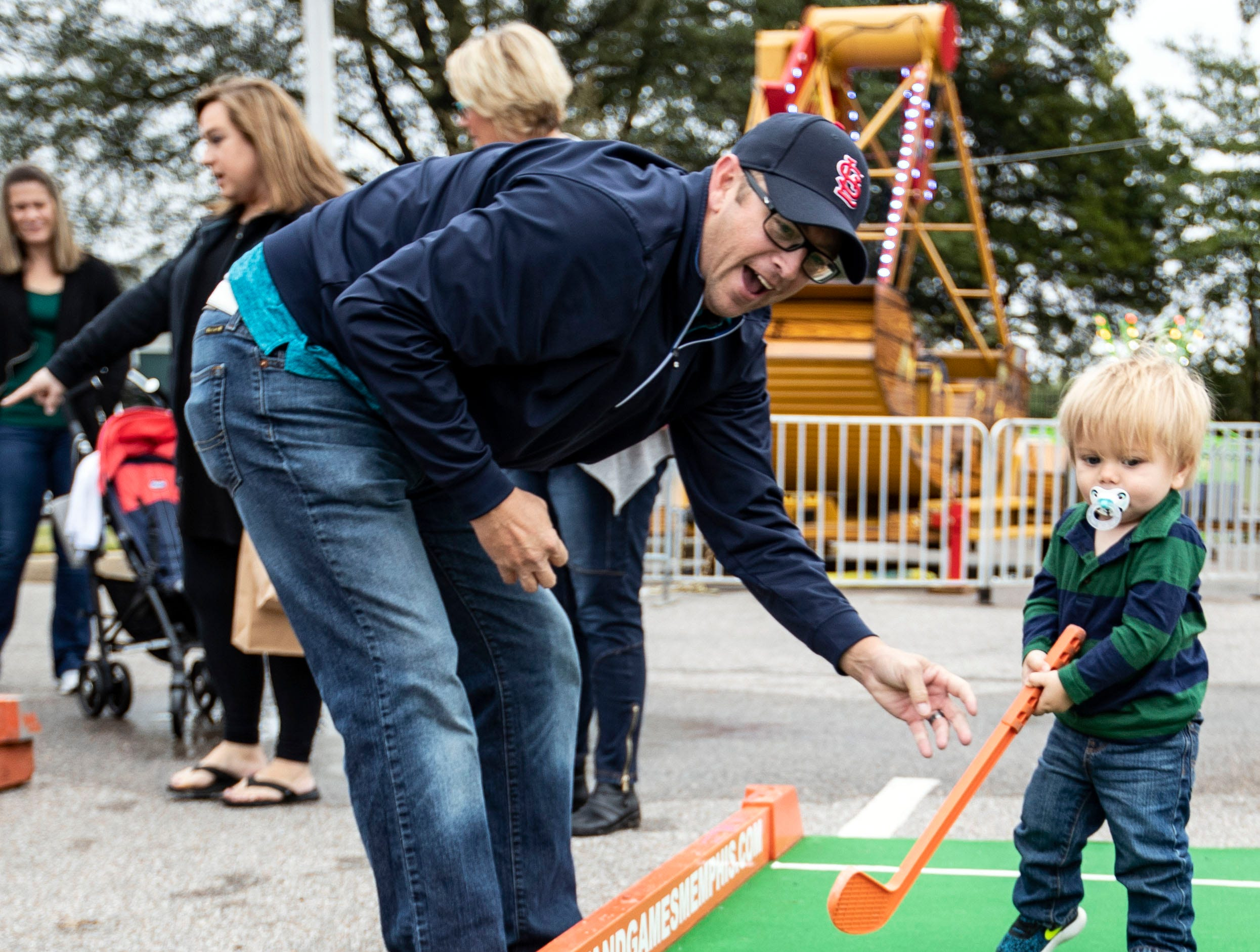 Jeremy Townsend assists his son Toby Townsend in a game miniature golf ball lands in the hole at the St. Ann Fall Fest Saturday October 20, 2018.