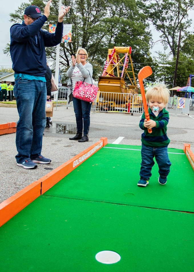 Jeremy Townsend celebrates with his son Toby Townsend after his ball lands in the hole at the St. Ann Fall Fest on Saturday October 20, 2018.