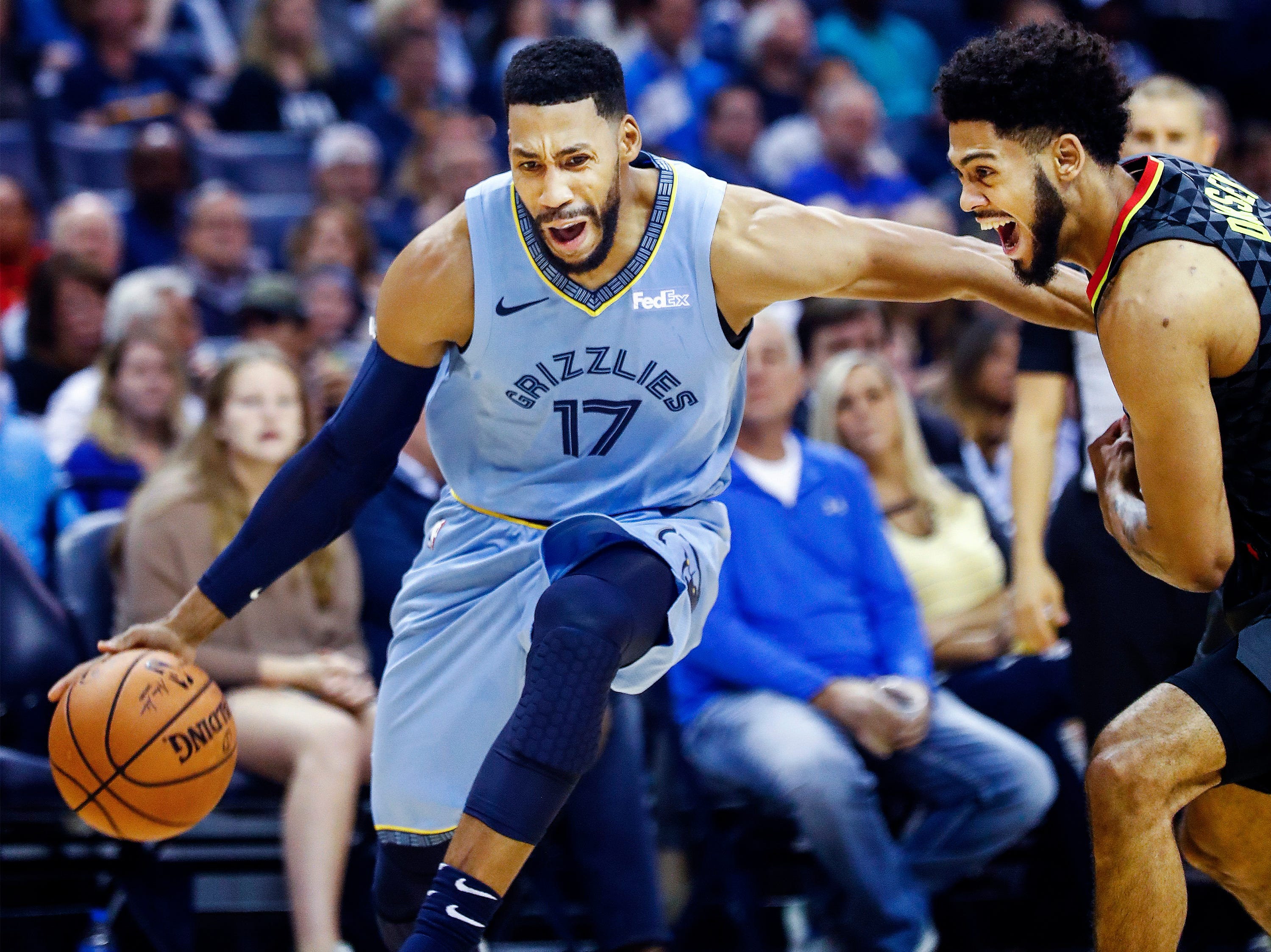 Memphis Grizzlies guard Garrett Temple (left) drives the lane against Atlanta Hawks defender Tyler Dorsey (right) in their home-opener at the FedExForum in Memphis, Tenn., Friday, October 19, 2018.