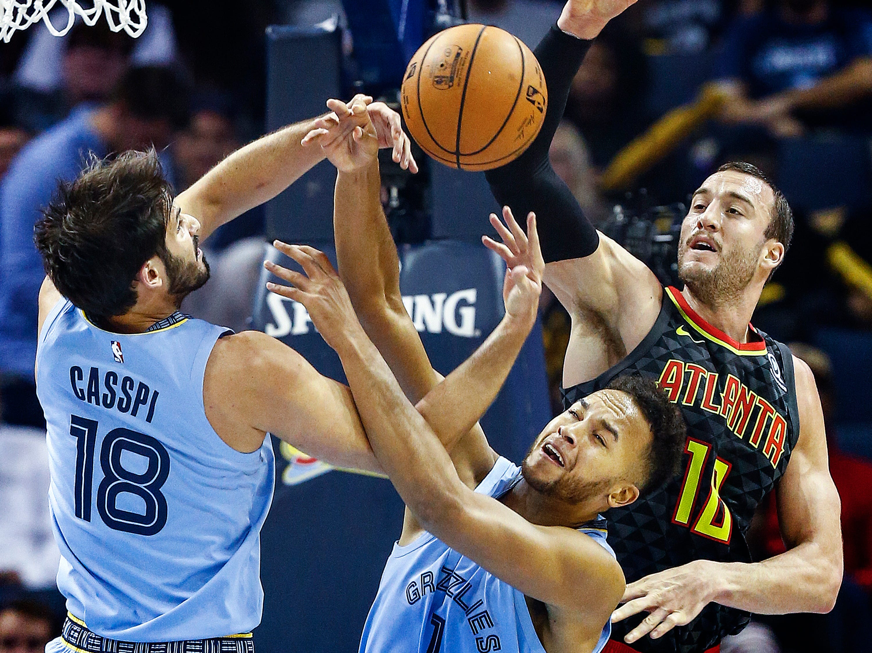 Memphis Grizzlies teammates Omri Casspi (left) and Kyle Anderson (middle) grab a rebound in front of Atlanta Hawks's Miles Plumlee (right) during action of their home-opener at the FedExForum in Memphis, Tenn., Friday, October 19, 2018.