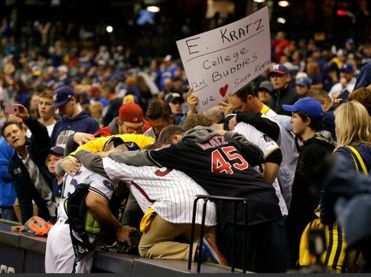 Brewers catcher Erik Kratz is greeted by his college friends before the game.