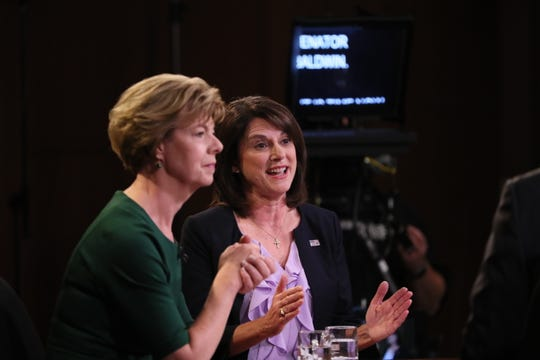 Sen. Tammy Baldwin, left, listens as Leah Vukmir responds to a question during the debate.