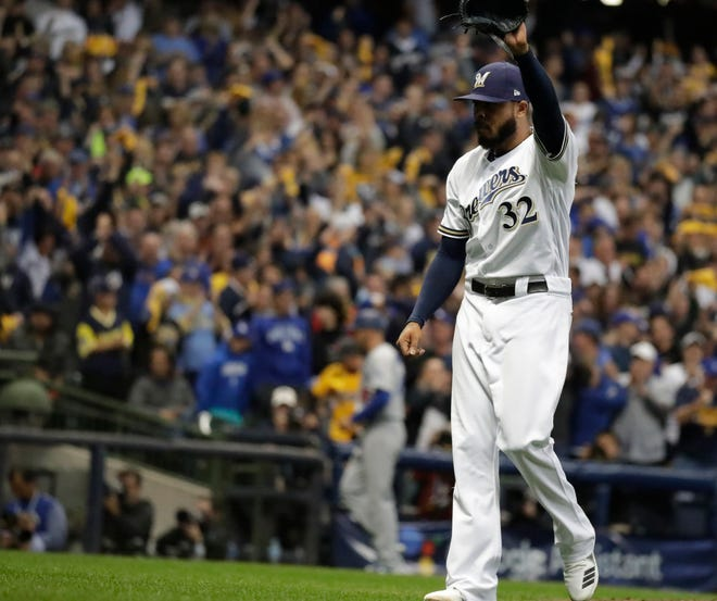 Milwaukee Brewers relief pitcher Jeremy Jeffress waves to the crowd after finishing off the seventh inning.