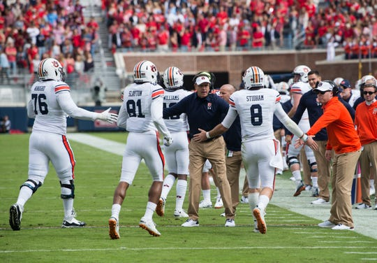 Auburn head coach Gus Malzahn high fives his team as they come off the field after a touchdown at Vaught-Hemingway Stadium in Oxford, Miss., on Saturday, Oct. 20, 2018.