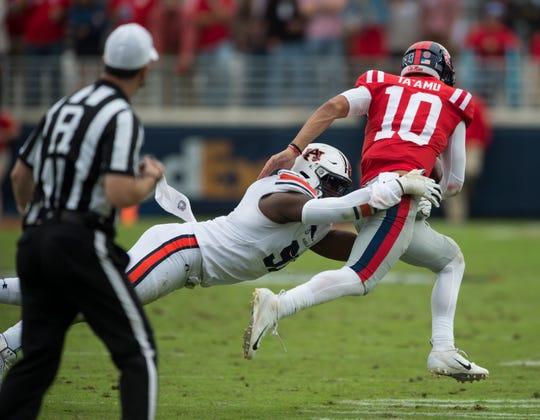 Auburn's Deshaun Davis (57) tackles Ole Miss' Jordan Ta'amu (10) at Vaught-Hemingway Stadium in Oxford, Miss., on Saturday, Oct. 20, 2018. Auburn defeated Ole Miss 31-16.