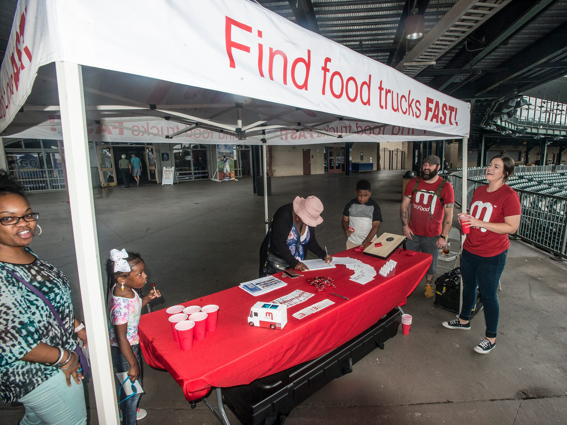 Guests play games at the mFood tent. Food Truck Mash-Up returned to Riverwalk Stadium on Saturday, Oct. 20, 2018, bringing a variety of food trucks, music and games for guests to enjoy.