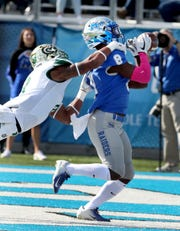 MTSU's Ty Lee (8) runs the ball in for a touchdown as Charlotte's Nafees Lyon (8) tackles Lee during the Homecoming game on Saturday, Oct. 20, 2018.
