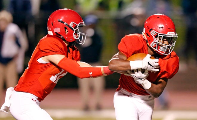 Brentwood Academy's Wade Wiliams hands the ball off to Tomario Pleasant as he runs for a touchdown during overtime in their game against Montgomery Bell Friday, Oct. 19, 2018, in Nashville, Tenn.