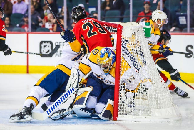 Predators goaltender Pekka Rinne guards his net as Flames center Dillon Dube (29) and Predators defenseman P.K. Subban (76) collide during the first period at Scotiabank Saddledome on Friday.