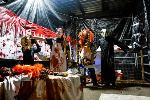"""Grace Levy, second from left, helps Bricen Presley with his mask as Mitchell Langford III, second from right, and James Levy get into position before the Haunted """"Gross"""" House opens at the Collier County Fairgrounds in Naples on Friday, Oct. 19, 2018."""